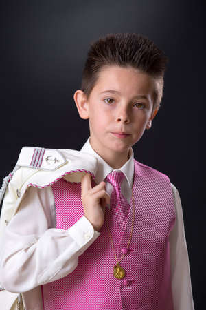 Young boy in his First Holy Communion holding his jacket over his shoulder and looking at camera on a black background.