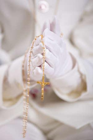 一个男孩的手的特写与白手套拿着一个金色的念珠为他的第一次圣餐。景深浅。