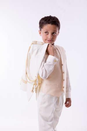 Jonge Eerste Communie jongen met zijn jas over zijn schouder op een witte achtergrond