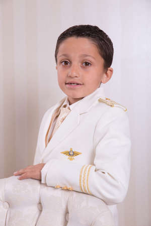 Young boy with serious expression standing and looking at camera in his First Holy Communion.