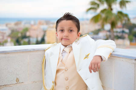 Young boy with white suit leaning on a wall with his elbow in his First Communion. Stock Photo
