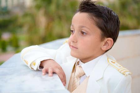 tiefe: Junge mit weißen Anzug in seiner Erstkommunion an einer Wand gelehnt. Geringe Schärfentiefe. Lizenzfreie Bilder