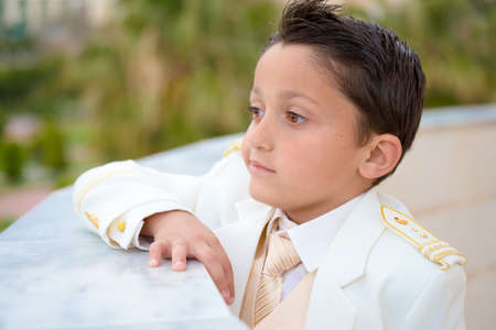 Young boy with white suit leaning on a wall in his First Communion. Shallow depth of field.