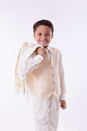 Young First Communion boy smiling with his jacket over his shoulder on white background Stock Photo