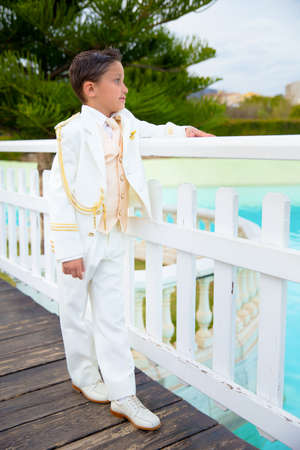 Young boy with white sailor suit leaning on a white wooden fence over a bridge in his First Communion Stock Photo