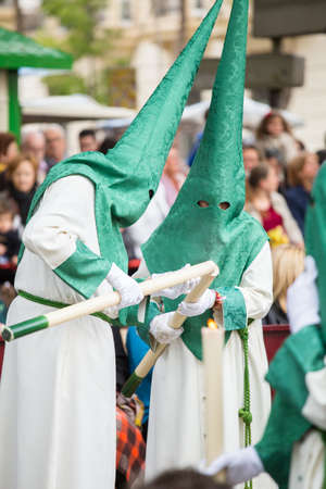 easter candle: Nazarenes lighting their candle on palm sunday (easter week). Holy Week in Spain. Stock Photo