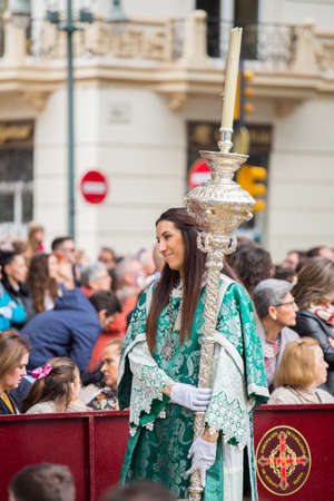 MALAGA, SPAIN - MARCH 20: Girl with silver staff participating in the procession of Palm Sunday (Pollinica) on March 20, 2016 in Malaga, Spain. Editorial