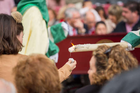 MALAGA, SPAIN - MARCH 20: Closeup of a nazarene giving candle wax  to an unidentified girl in the procession of Palm Sunday (Pollinica) on March 20, 2016 in Malaga, Spain. Editorial