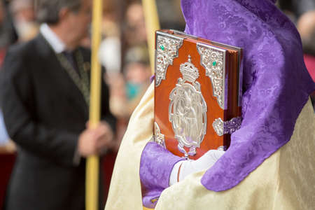 MALAGA, SPAIN - MARCH 20: Nazarene holding a wooden box with silver ornaments in the procession of Palm Sunday (Pollinica) on March 20, 2016 in Malaga, Spain. Editorial