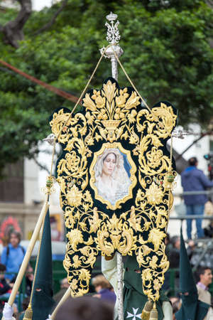 MALAGA, SPAIN - MARCH 20: Nazarenes holding a banner of the Virgin Mary in the procession of Palm Sunday (Pollinica) on March 20, 2016 in Malaga, Spain.