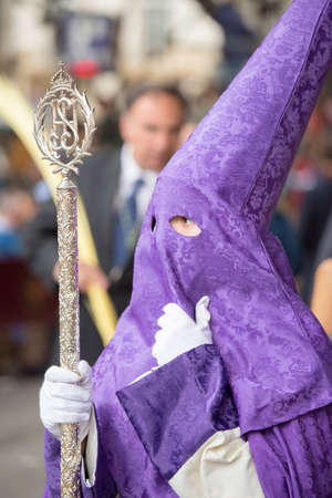 seville: MALAGA, SPAIN - MARCH 20: Nazarene with silver staff participating in the procession of Palm Sunday (Pollinica) on March 20, 2016 in Malaga, Spain.