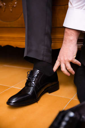 Man putting his black shoes. Hands closeup. People, business, fashion and clothing concept.