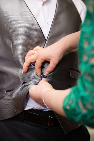 Hands of mother helping his son with his vest before wedding ceremony