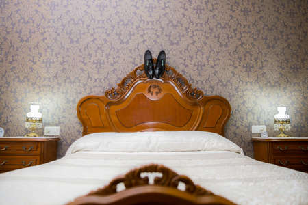 Vintage room on wedding day with groom shoes hanging on headboard