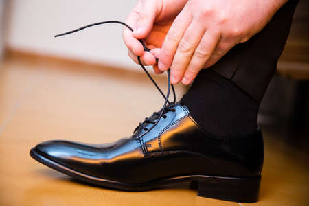 Groom putting his wedding shoes. Hands closeup. Stock Photo