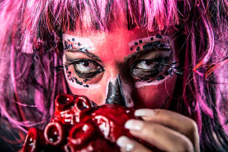 Closeup of a woman with sugar skull makeup holding a bloody heart in front of her mouth. Shallow depth of field.