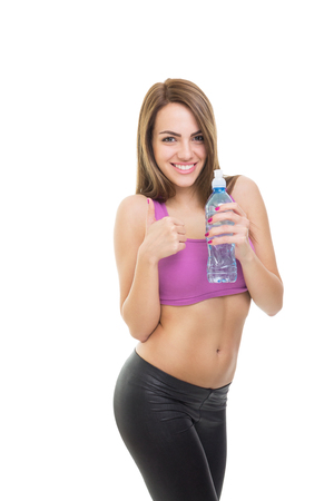 Attractive happy young Caucasian brunette fitness woman holding water bottle gesturing thumb up  Fitness and diet concept  Isolated on white background  Stock Photo