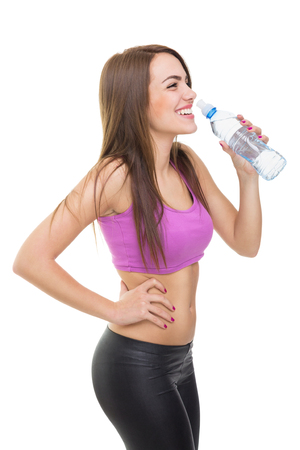 Spontaneous candid shot of young Caucasian brunette woman drinking water during workout smiling looking sideways  Isolated on white background  Diet and healthy lifestyle concept
