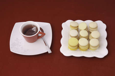 Cup of tea and stacked and aligned macaroons on a velvet tableclothe  photo