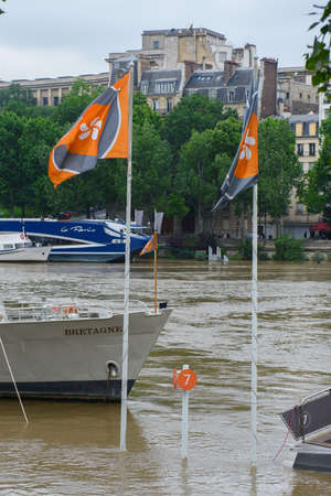 PARIS - JUNE 4: Paris flood with high water on June 4, 2016 in Paris, France. Flags of the parisian boats