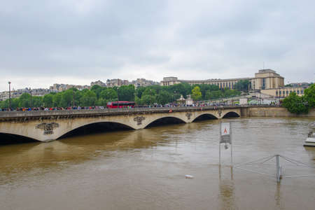 PARIS, FRANCE - JUNE 4: Paris flood with high water on June 4, 2016 in Paris, France. Iena bridge and people looking the floods