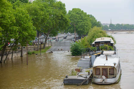 PARIS, FRANCE - JUNE 4: Paris flood with high water on June 4, 2016 in Paris, France. Flooded road and barge