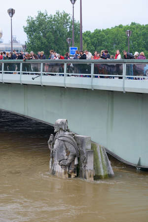 PARIS, FRANCE - JUNE 4: Paris flood with high water on June 4, 2016 in Paris, France.  People looking the Zouave statue on the Alma Bridge