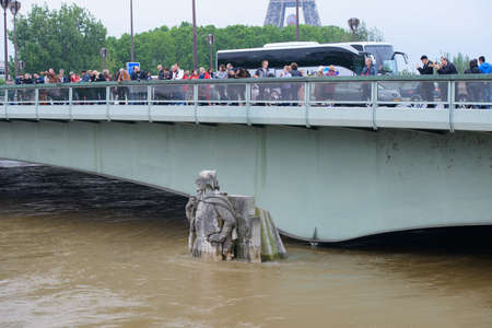 personas tomando agua: PARIS, FRANCE - JUNE 4: Paris flood with high water on June 4, 2016 in Paris, France.  Zouave statue of the Alma Bridge and people taking photos