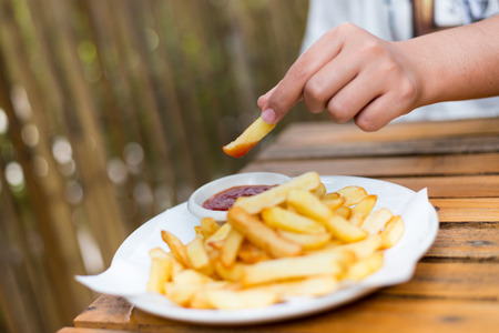 hand holding french fries dip to tomato sauce.