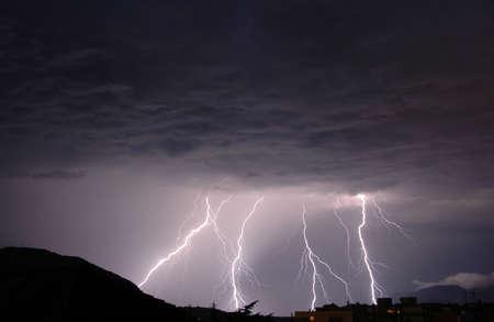 Lightnings in a dark thunderous night photo