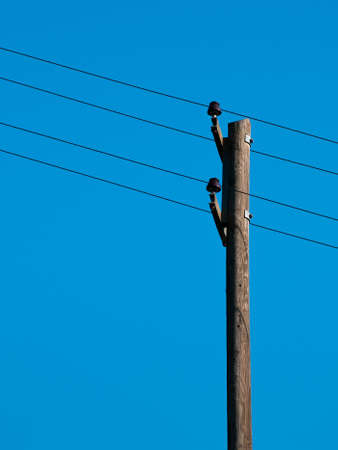 telephone pole: Old telegraph pole on blue sky with four oblique cables