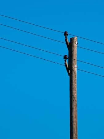telegraaf: Oude paal op de blauwe hemel met vier schuine kabels Stockfoto