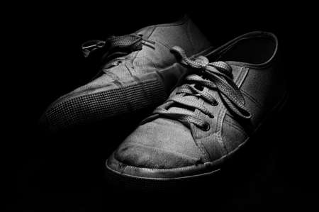 Old and used white tennis shoes on black background Stock Photo - 16789660