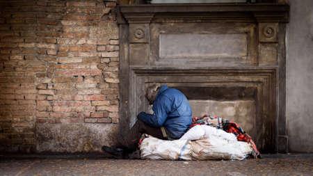 persona triste: Pobre hombre sin hogar en la calle con sus bolsas