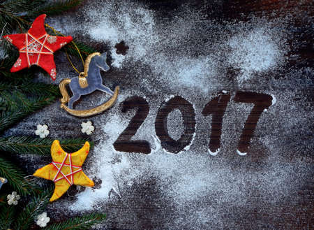 papiermache: New Year and Christmas background. Greeting card with xmas ornaments, conifer branches. Winter holidays concept. Year 2017 of rooster. Space for text.