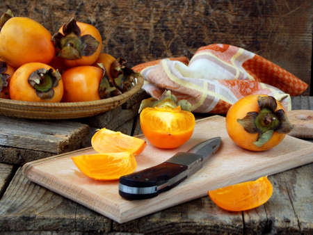 Delicious ripe orange persimmons in bowl on wooden background. Selective focus