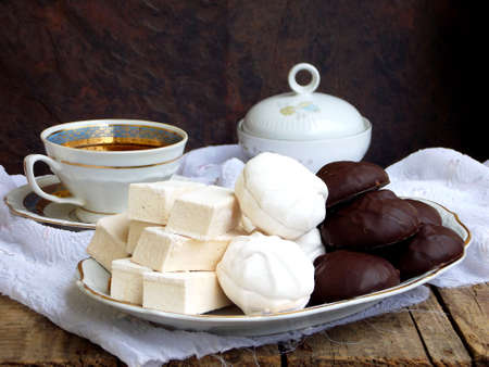 Sweet white Russian marshmallow, chocolate zephyr, meringue, apple pastila and cup of coffee on wooden background. Selective focus