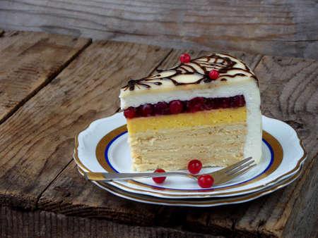 piece of cake Napoleon: crispy cakes with cream, orange cream, cranberry jelly, cheese mousse. Side view. Selective focus