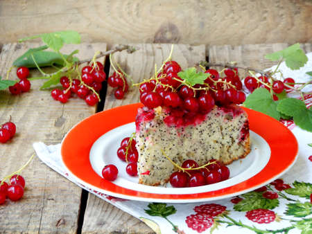 poppy seeds: Piece of cake or sponge cake with red currants and poppy seeds on a wooden background