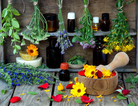bunches of healing herbs - mint, yarrow, lavender, clover, hyssop, milfoil, mortar with flowers of calendula and bottles, herbal medicine