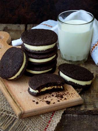 Homemade Oreo chocolate cookies with white marshmallow cream and glass of milk on dark background.
