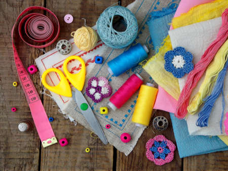 Pink, yellow and blue accessories for needlework on brown wooden background. Knitting, embroidery, sewing. Small business. Income from hobby.