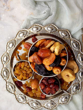 A composition from different varieties of dried fruits on a wooden background - dates, figs, apricots, prunes, raisins, cranberries. Healty food.