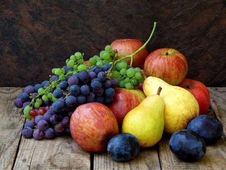 Bodegón de frutas de otoño: uvas, manzanas, pera, ciruela sobre un fondo de madera. enfoque selectivo