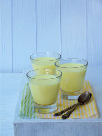 Yellow dessert Junket from milk and rennet extract with turmeric in glasses on light background. Jelly-like pudding made from sweet cottage cheese. Healthy food. Space for text.