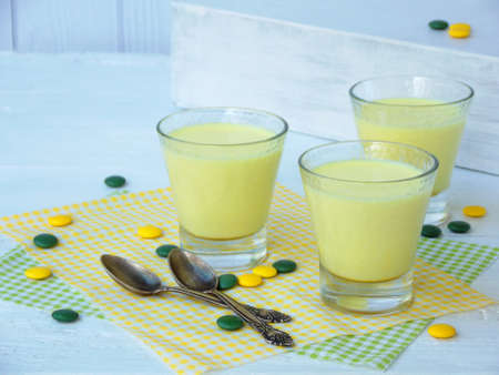 Yellow dessert Junket from milk and rennet extract with turmeric in glasses on light background. Jelly-like pudding made from sweet cottage cheese. Healthy food Stock Photo