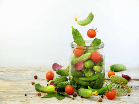 Cucumbers and cherry tomatoes with herbs and spices for pickling in glass jar with flying ingredients on a white background.