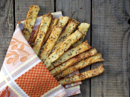 grissini: Crispy bread sticks of puff pastry sprinkled with salt and caraway seeds on wooden background. Stock Photo