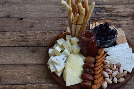 cheeseboard: Cheese plates served with grissini, crackers, dates, jam, olives and nuts on wooden background.