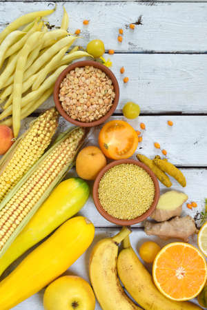 Composition of yellow vegetables, beans and fruits - banana, corn, lemon, plum, apricot, pepper, zucchini, tomato, asparagus bean, millet, soybeans peas ginger Healthy food Top view Flat lay Stock Photo
